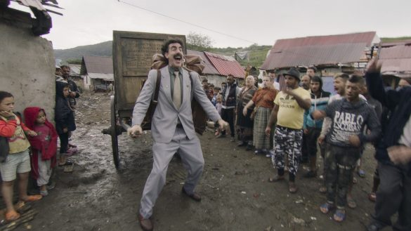 Sacha Baron Cohen as Borat. He is wearing a grey suit and is pulling a wooden carriage behind him as villagers boo angrily