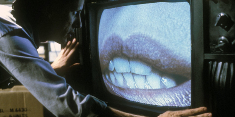 James Woods in Videodrome (1983). He is too in front of an old TV that has a close up of a pair of woman's lips on.