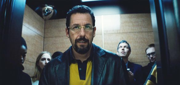 Adam Sandler in Uncut Gems (2019) wearing a leather jacket and a yellow shirt with a black collar.