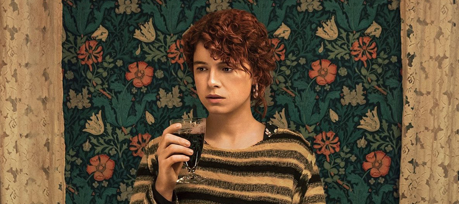 Jessie Buckley sat against a floral wallpaper wall holding a glass or red win in I'm Thinking of Ending Things